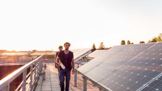 stockvideo's en b-roll-footage met ws engineering students walking between solar panels on rooftop - ingenieurswerk