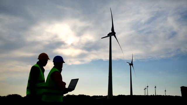 vídeos de stock, filmes e b-roll de engenharia usando laptop no campo de turbinas eólicas - usar laptop