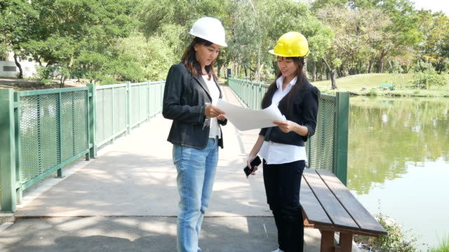 engineers and architect on construction site with plan