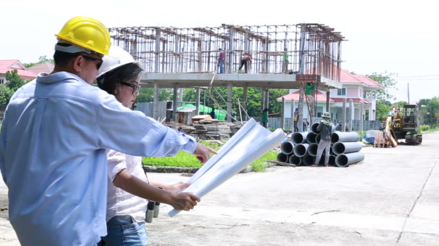engineers and engineers and architect on construction site with plan