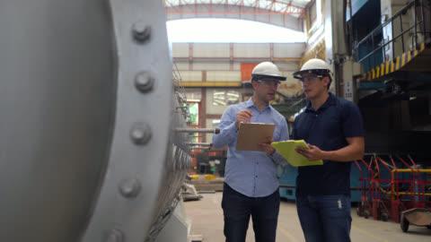 vidéos et rushes de ingénieurs à une usine métallurgique vérifiant la structure construite prenant des notes sur le presse-papiers - montrer la voie