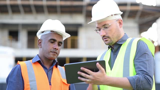 engineers at construction site, using digital tablet - construction worker stock videos & royalty-free footage
