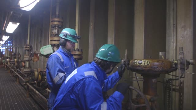 engineers check the valves on pipes on the towel deck of the armada gas condensate platform operated by bg group plc in the north sea off the coast... - valve stock videos & royalty-free footage