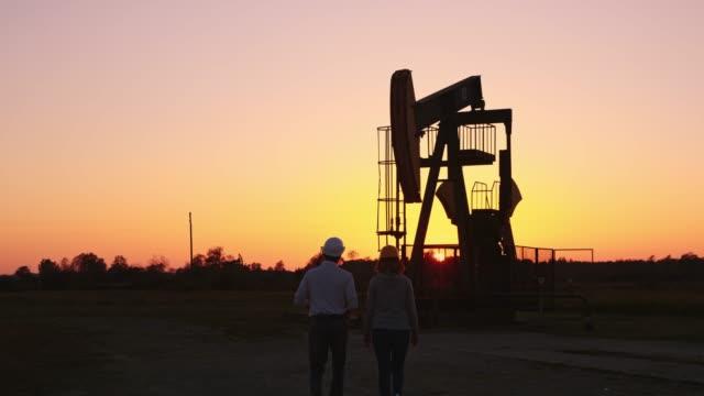 Engenheiros de WS verificando o poço de petróleo unidade de bombeamento ao entardecer