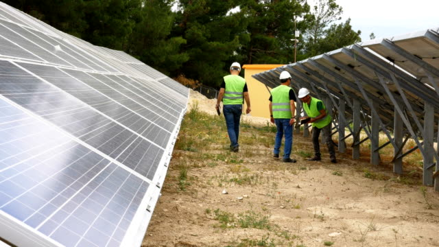 Engineers checks the solar panels in the field ,Environmentally friendly electricity production , Sustainable Renewable Energy