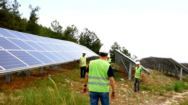 engineers checks the solar panels in the field ,environmentally friendly electricity production , sustainable renewable energy - finance and economy stock videos & royalty-free footage