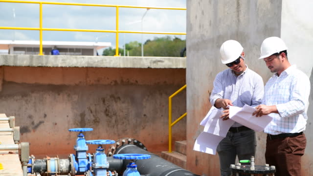 vídeos de stock e filmes b-roll de engineers discussing and talking on blueprint at construction site - águas residuais