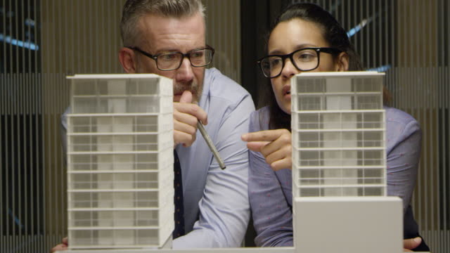 engineers examining model building in office - architetto video stock e b–roll