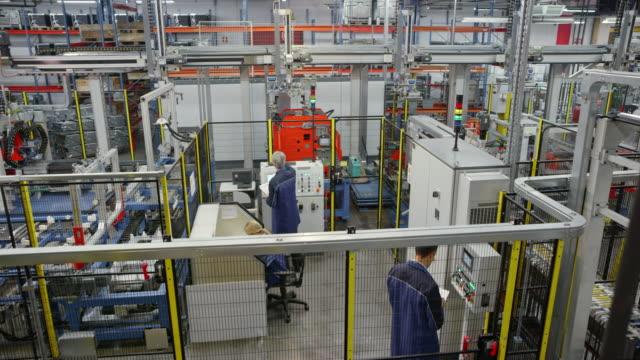 cs-ingenieure in der fabrik, die bedienung der maschinen - halle gebäude stock-videos und b-roll-filmmaterial