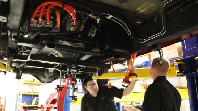 stockvideo's en b-roll-footage met engineers inspect the space where a 350 volt batter will go between the gas engine, and a new electric motor, that was installed in coca cola... - orem utah
