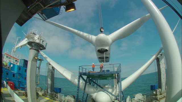 engineers keep watch as the blades of a wind turbine are lifted into the air. - engineering stock videos & royalty-free footage