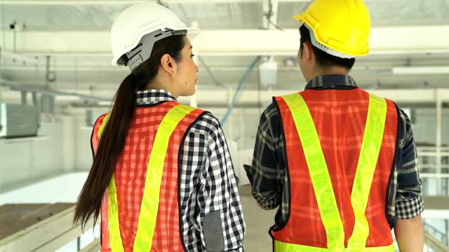 技術者は、工事現場での会議します。同僚を議論します。ボス ・ ワーカーを主張します。team.wear ヘルメットでの会話は、机上の計画を保持します。 - 説明する点の映像素材/bロール