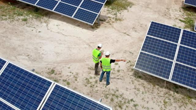 stockvideo's en b-roll-footage met ingenieurs vergadering op zonne-energiecentrale - zonne energie