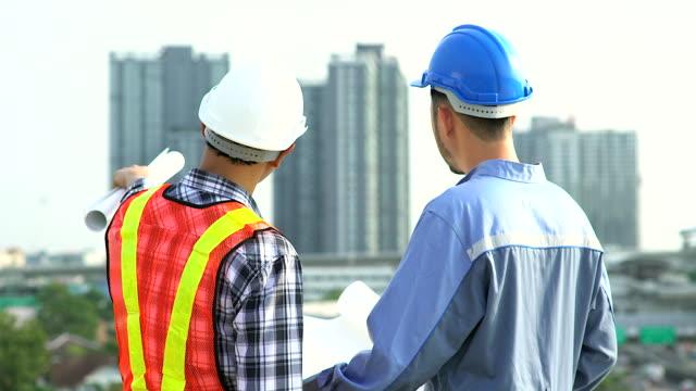 Ingenieurs permanent op terras bovenop de bouwplaats. Collega's bespreken. Werkgever en werknemer stellen. op zoek naar zijn blauwdruk met helm greep papier plannen