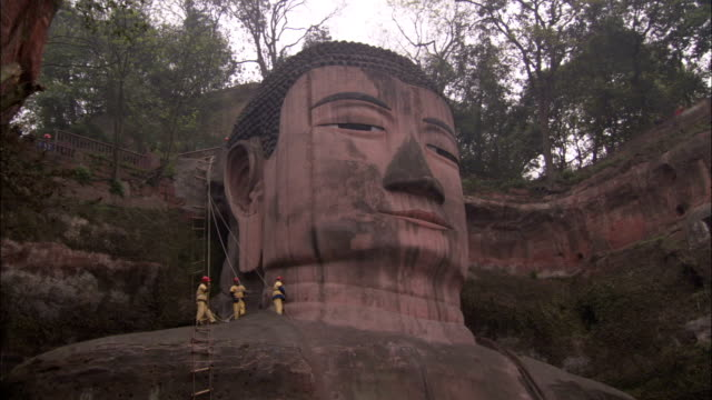 engineers standing on the shoulder of a leshan giant buddha statue secured by ropes clean a section of it's neck with brushes.\n available in hd. - ingegnere video stock e b–roll