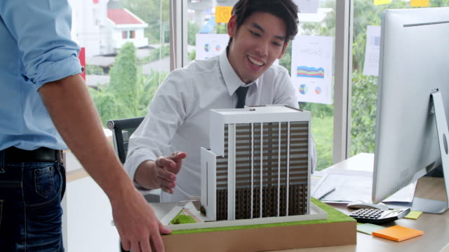 Engineers Team Working. male architect and colleague constructing an architectural model