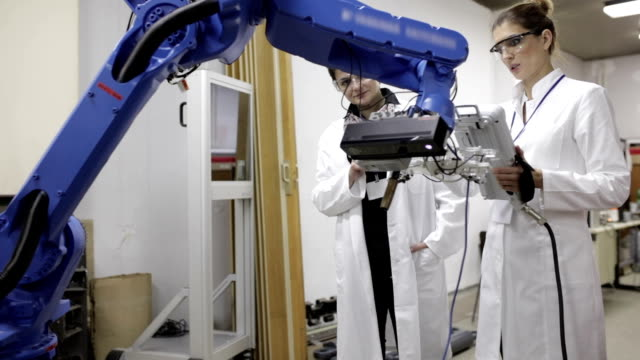 vídeos de stock e filmes b-roll de engineers testing robotic arm, panning shot - stem assunto