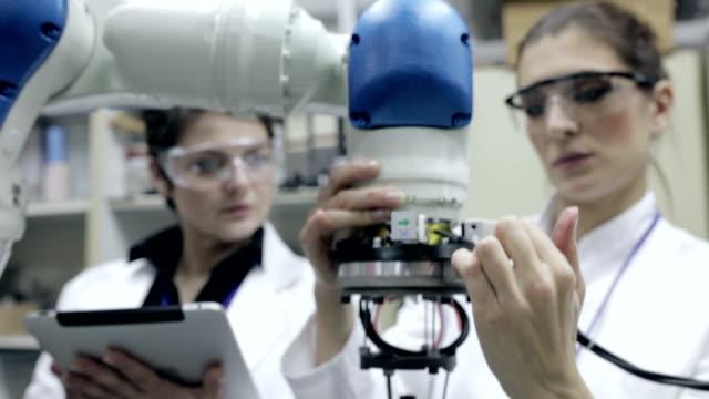 ingenieure testen roboterarm, panning shot - maschinenbau stock-videos und b-roll-filmmaterial