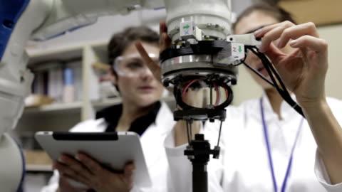 engineers testing robotic arm, panning shot - industrial equipment stock videos & royalty-free footage