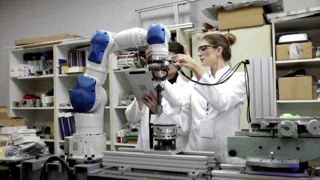 ingenieure testen roboterarm, panning shot - research stock-videos und b-roll-filmmaterial
