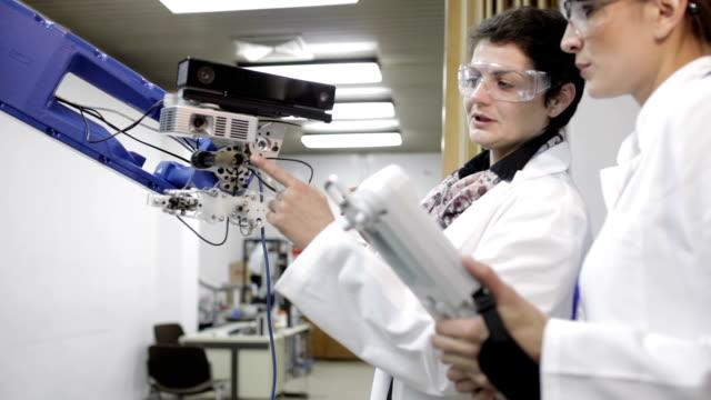 vídeos de stock e filmes b-roll de engineers testing robotic arm, panning shot - controlo de qualidade