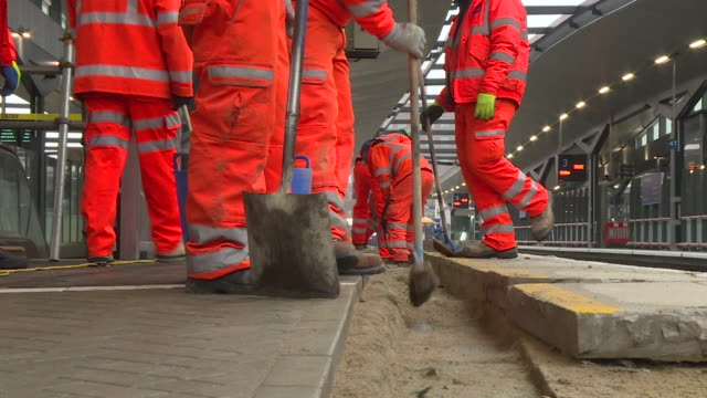 Engineers use brooms spades and drills to make alterations to a platform at London Bridge Station December 2017 NNPX190D Clip taken from programme...