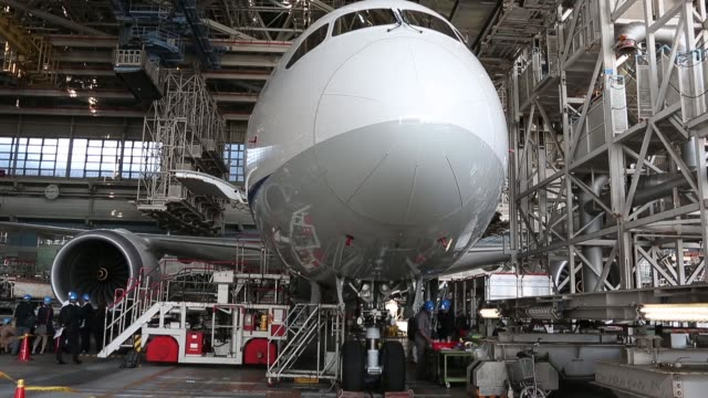 vídeos de stock, filmes e b-roll de engineers work on a boeing co. 787 dreamliner aircraft operated by all nippon airways co. to install the newly redesigned battery in a hanger at... - boeing 787