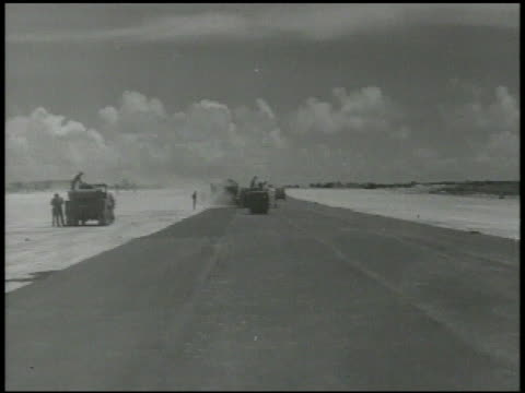 vídeos de stock e filmes b-roll de engineers workers laying down pavement paving new airstrip tarmac for military airbase male driving steamroller mariana islands world war ii wwii... - cilindro veículo terrestre comercial