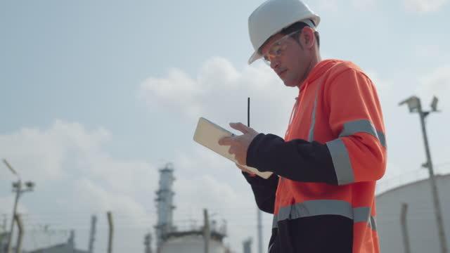 vidéos et rushes de ingénieurs travailleurs en plein air à l'usine industrielle, pétrolière ou gazière. - sûreté