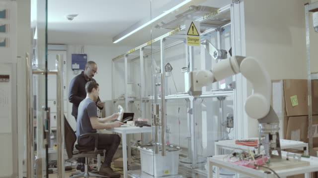 engineers working on a design for robotic arm in office - robotics stock videos & royalty-free footage