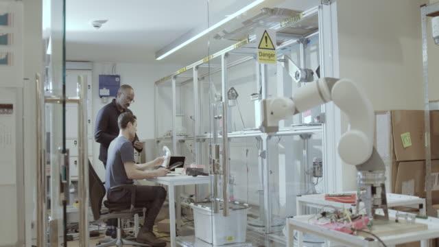 vídeos y material grabado en eventos de stock de engineers working on a design for robotic arm in office - robótica