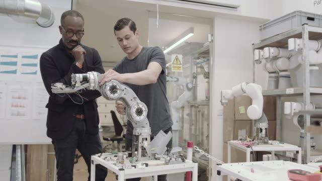 vídeos y material grabado en eventos de stock de engineers working on a robotic arm - robótica