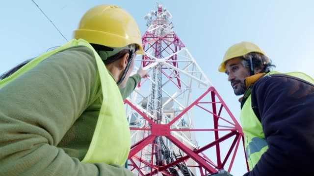 engineers working on the field near a telecommunications tower. teamwork. - telecommunications equipment stock videos & royalty-free footage