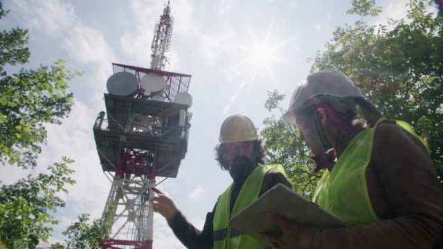 engineers working on the field near a telecommunications tower. teamwork. - mast stock videos & royalty-free footage