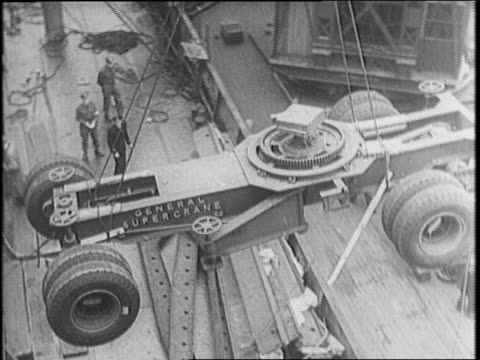stockvideo's en b-roll-footage met england / american lend-lease plane unloaded by a crane war correspondents watching, writing / crane lowers truck chassis / tank is lowered / tanks... - chassis