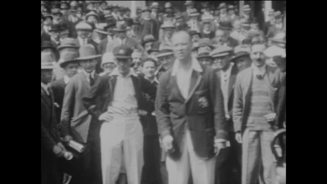 vídeos de stock, filmes e b-roll de england captain aw carr tosses the coin with the captain of australia hl collins watched by an excited crowd of people in front of the pavilion on... - lançar a moeda ao ar