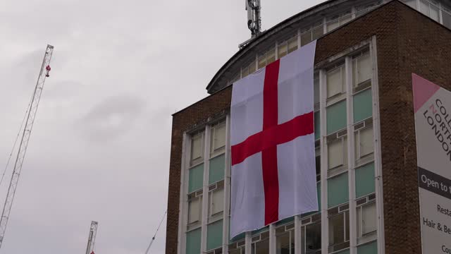 england flag hangs from a building as fan arrive at wembley stadium for the 2021 uefa european football championship final match between england and... - hanging stock videos & royalty-free footage