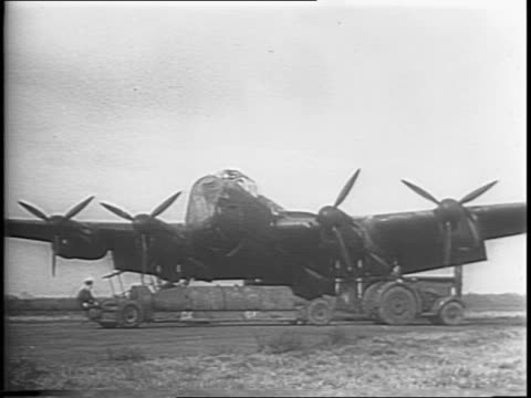 england / montage of a huge bomb being brought out to a plane, soldiers standing around the bomb, bomb attached to undercarriage of plane / montage... - 1944 bildbanksvideor och videomaterial från bakom kulisserna