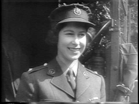 england / princess elizabeth removes a tire from a truck, checks oil, looks through engine / elizabeth with family including sister margaret rose,... - world war ii stock videos & royalty-free footage