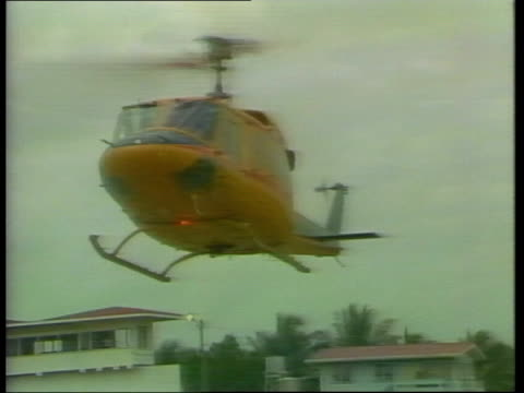 berbice a/g cricket pitch g/a team helicopter landing ms ian botham and west indian players out ms jackman lr with pocket camera ms jackman and two... - テストクリケット点の映像素材/bロール