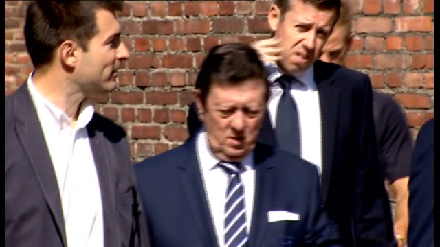 england team visit auschwitz concentration camp people leaving building / hodgson and bernstein along / england players departing building and along... - leaving prison stock videos & royalty-free footage