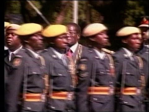 England tour to Zimbabwe close to collapse/Closeup look at regime ITN LIB President Robert Mugabe inspecting troops TCMS SIDE Mugabe along at rally...
