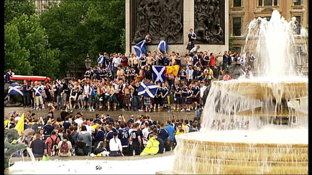 England v Scotland friendly Reporter to camera Vox Pops Bagpipe players with fans holding Scottish Lion flag Scottish fans crowded around Nelson's...