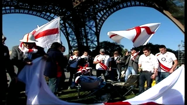 England v South Africa buildup FRANCE Paris EXT England fan in top hat stands below Eiffel Tower holding England flag England fans gathered below...