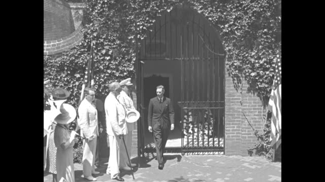 England's King George VI and wife Queen Elizabeth and other people stand around on lawn in front of Mount Vernon mansion / CU inscription on wall of...