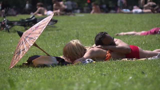 englischer garten, a couple lying on earth,  summer,  sunny, park,  lawn - ミュンヘン エングリッシャーガルテン点の映像素材/bロール