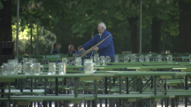 englischer garten - chinesischer turm, biergarten, man cleans up, empty benches and tables, many jars - ミュンヘン エングリッシャーガルテン点の映像素材/bロール