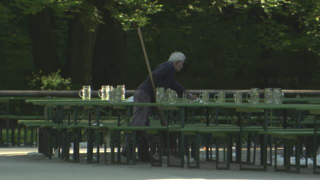 vídeos de stock e filmes b-roll de englischer garten - chinesischer turm, biergarten, man cleans up, empty benches and tables, many jars - homens de idade mediana