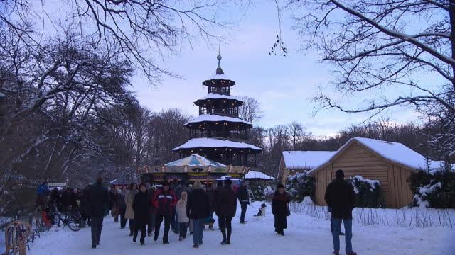 englischer garten - chinesischer turm, christmas market, snow, walking people, biergarten - ミュンヘン エングリッシャーガルテン点の映像素材/bロール