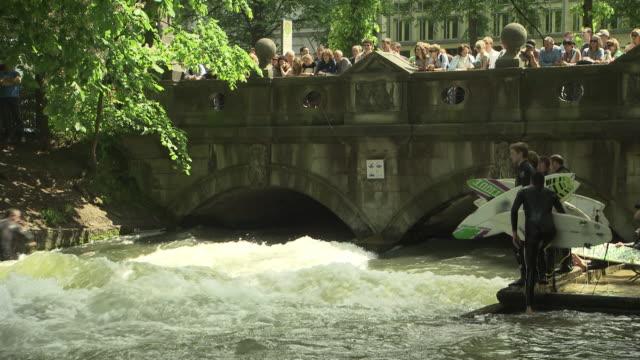 englischer garten - eisbach, surfer are waiting, surfboards, viewer, river, water, bridge, trees - ミュンヘン エングリッシャーガルテン点の映像素材/bロール